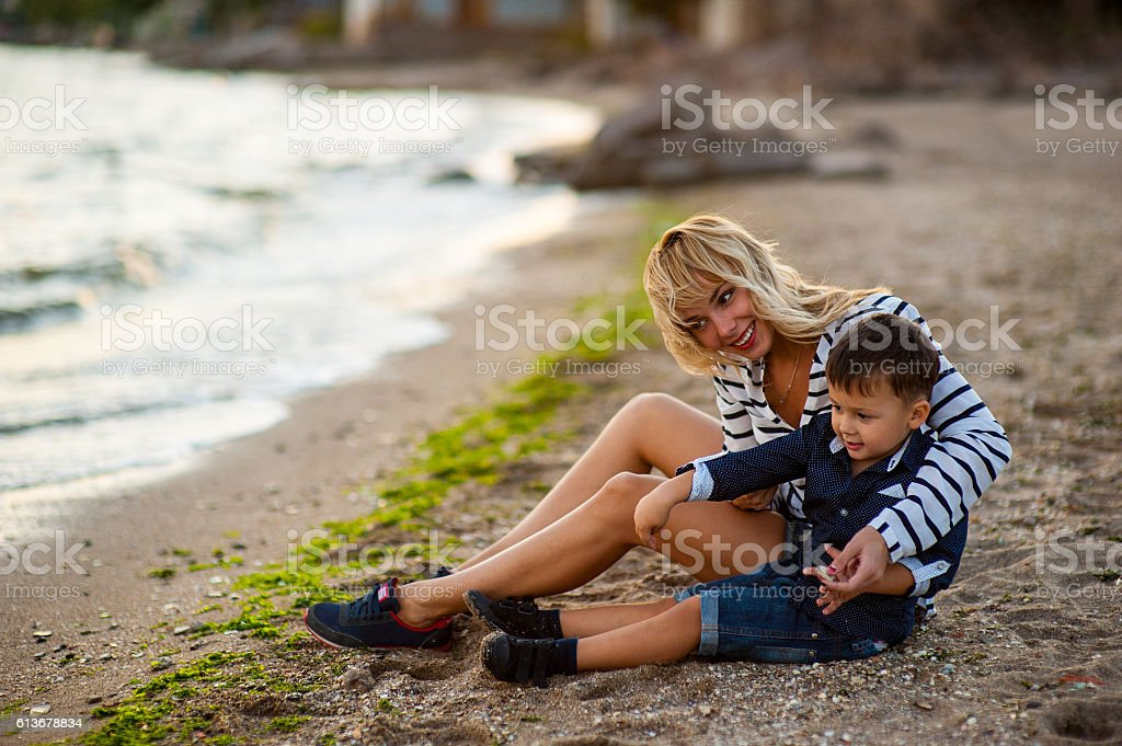 woman with a child  playing on the beach stock photo