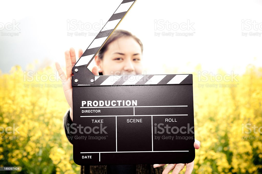 A woman with a clapper board outside royalty-free stock photo