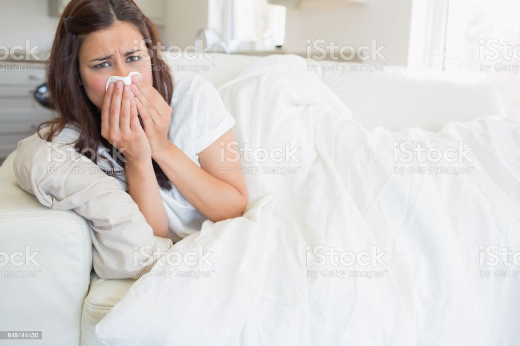 Woman with a cold lying on sofa stock photo