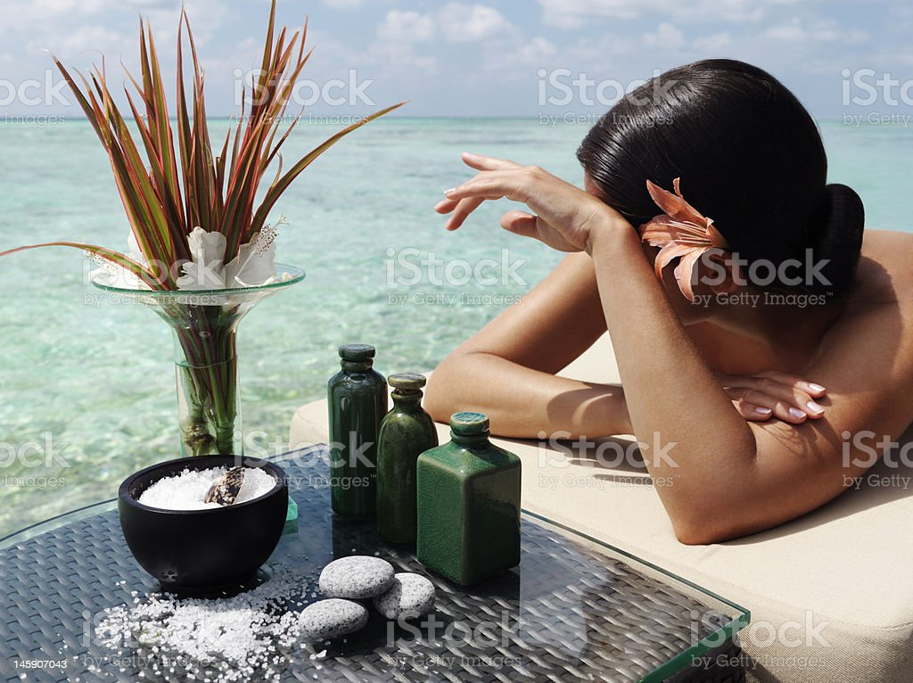 A woman with a flower in her hair in a pool next to spa item royalty-free stock photo