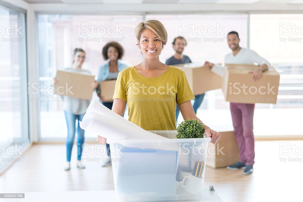 Woman with a group of coworkers moving office stock photo