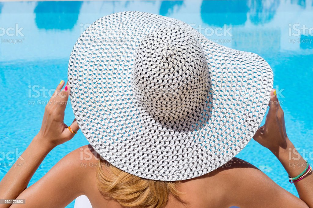 Woman with a hat at the swimming pool stock photo