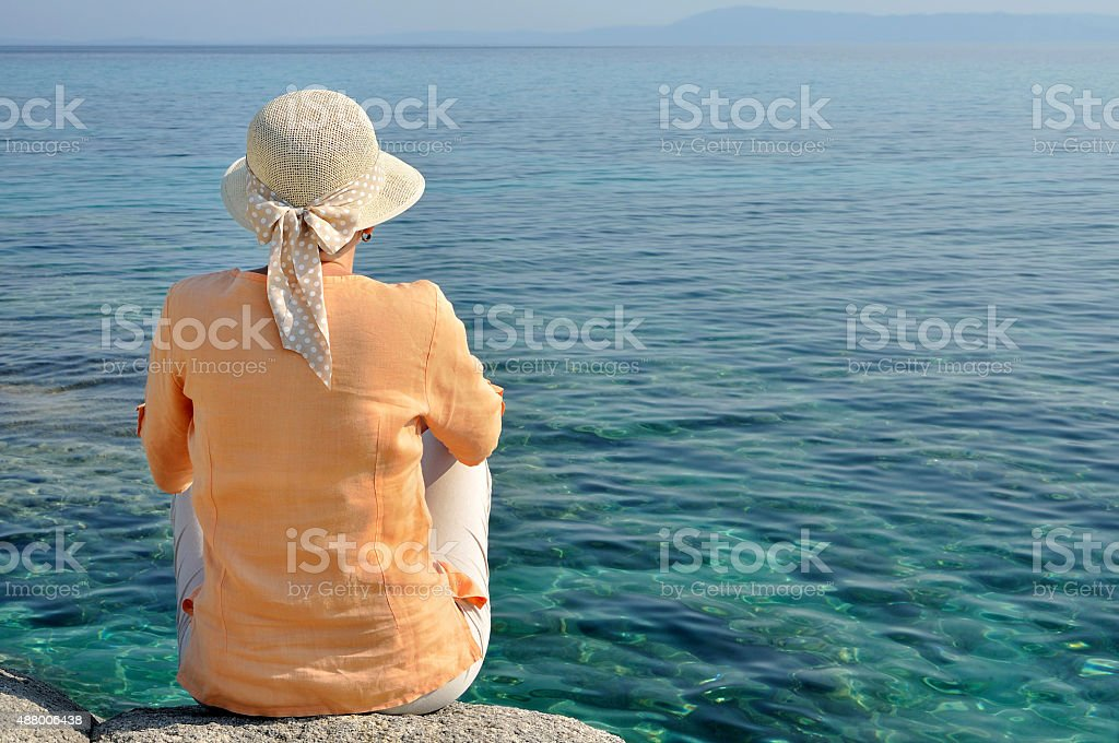 Woman with a hat facing the sea meditating stock photo