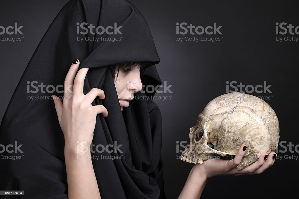 Woman with a human cranium in black stock photo