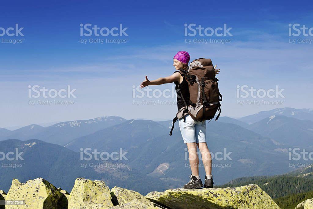 A woman with a large backpack hiking at the top of a rock royalty-free stock photo