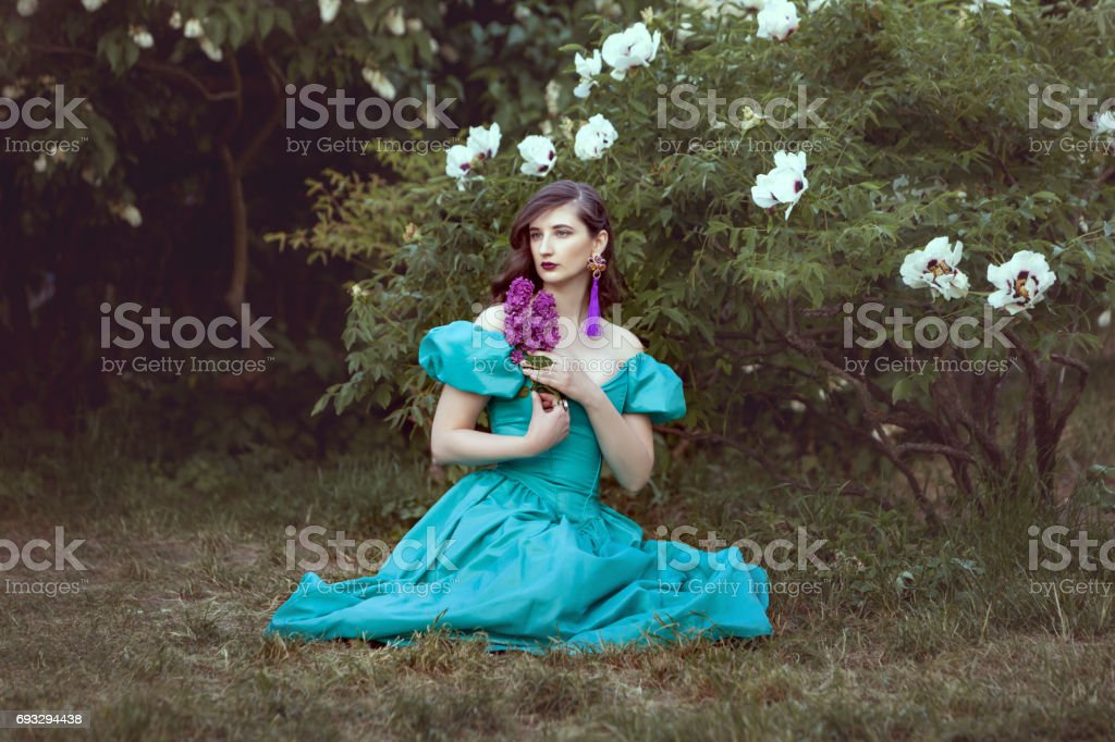 Woman with a lilac sits on the grass. stock photo