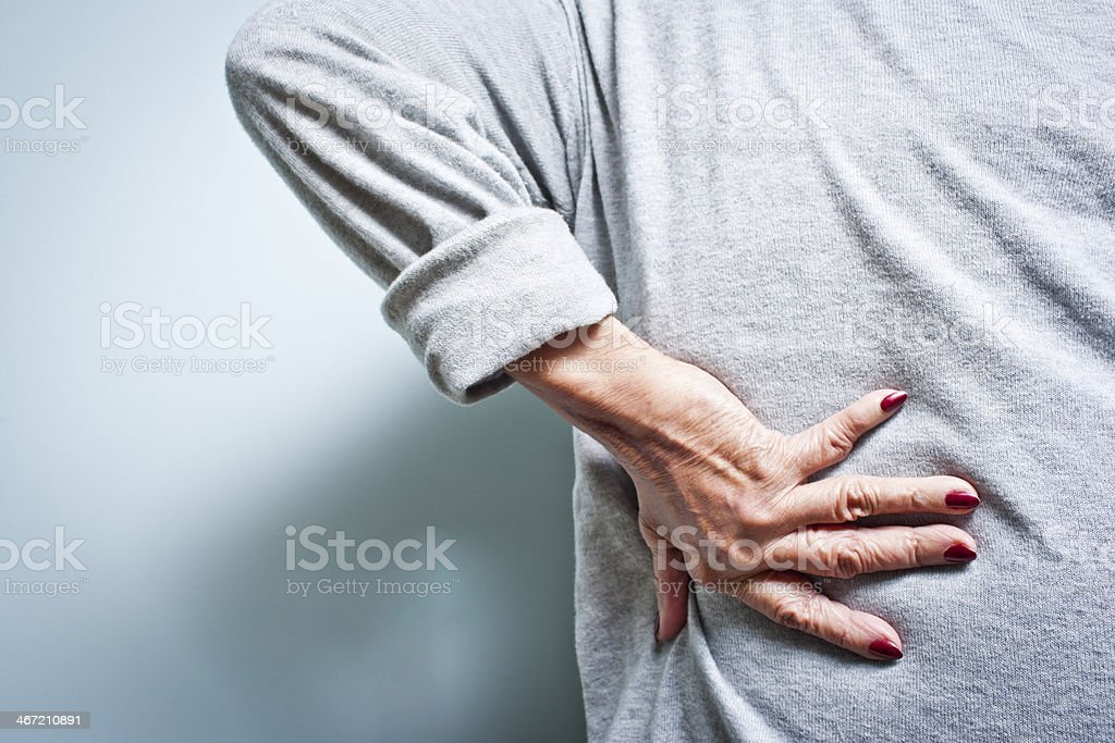 Woman with a lower back ache bent over in pain stock photo