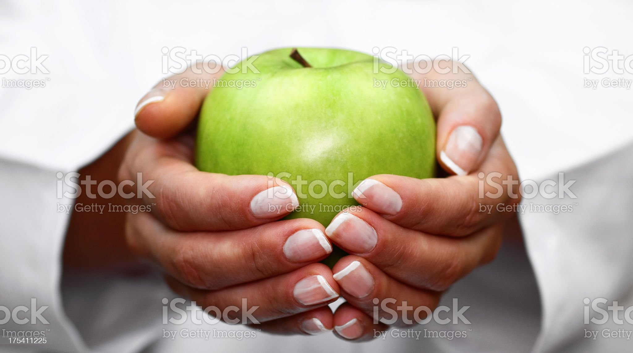 A woman with a manicure holding a green apple in her hands royalty-free stock photo