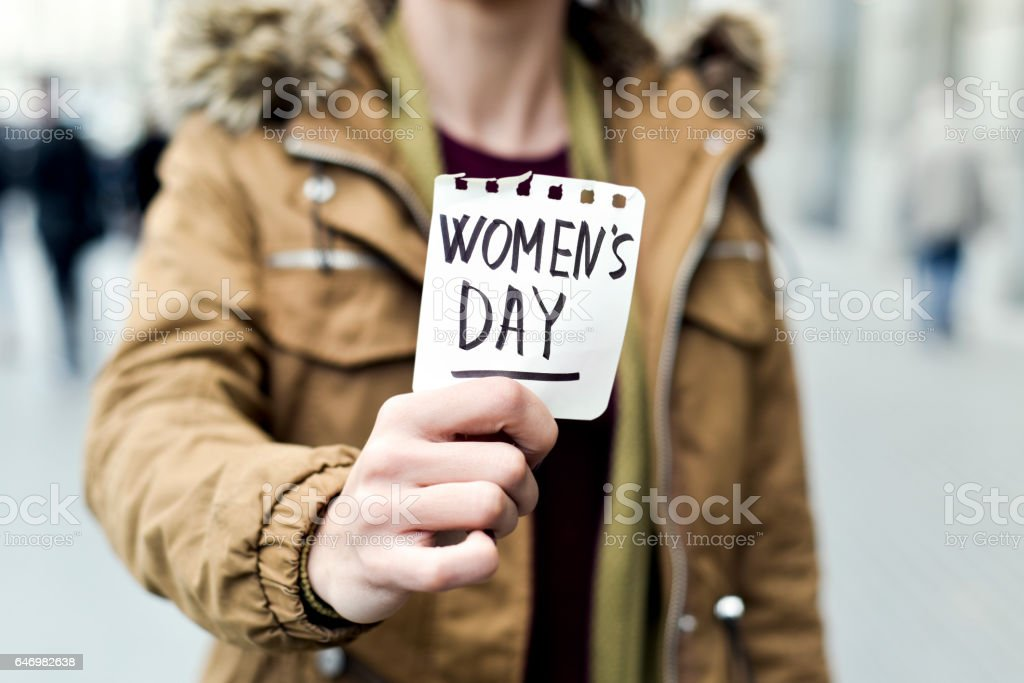 woman with a note with the text womens day stock photo