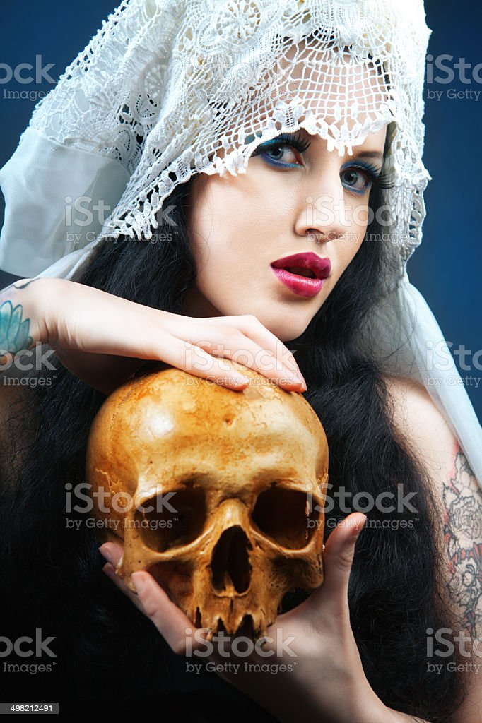 Woman with a pale face and skull. stock photo