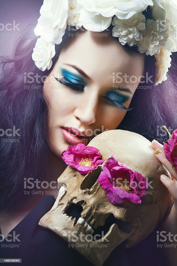 Woman with a pale face and skull stock photo