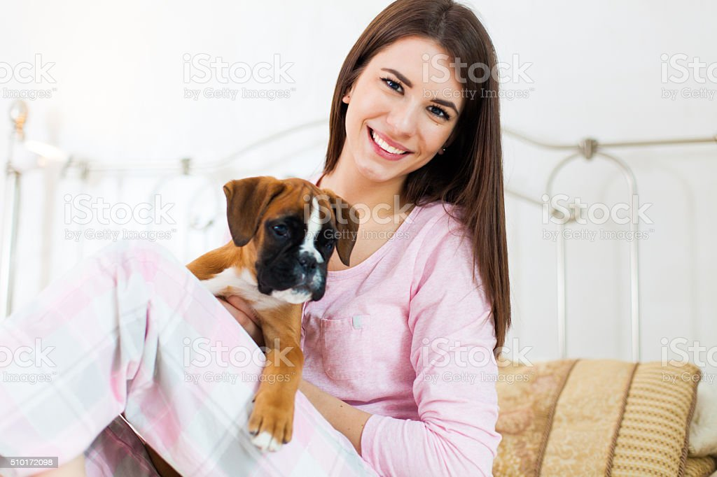 Woman with a puppy in bedroom stock photo