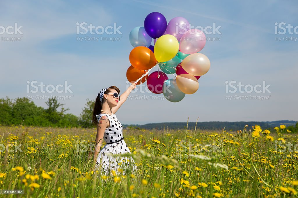 woman with a rockabilly dot dress and lot of balloons stock photo