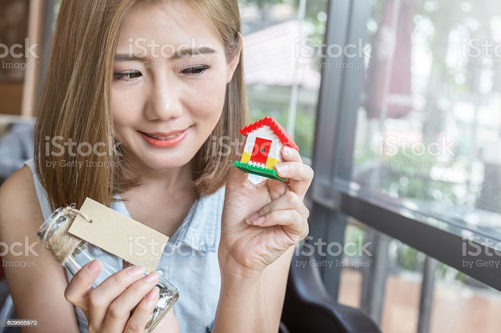 woman with a small house thinking stock photo
