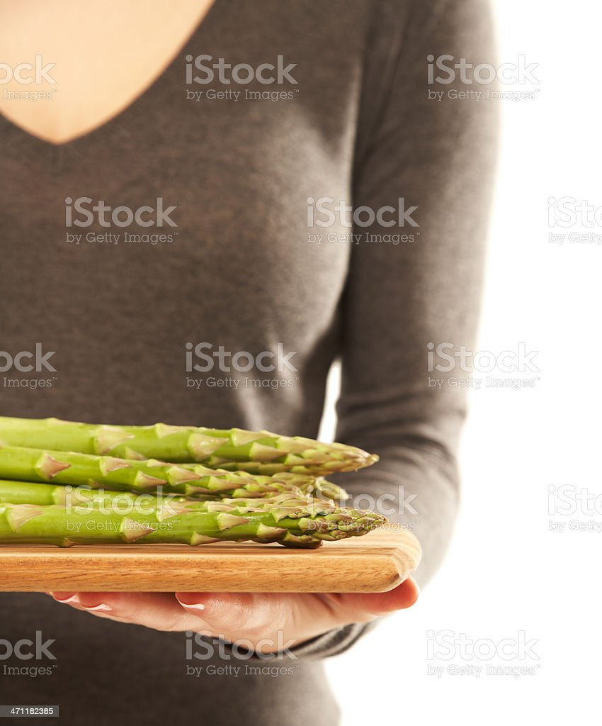 Woman with a tray full of fresh asparagus. Isolated. royalty-free stock photo