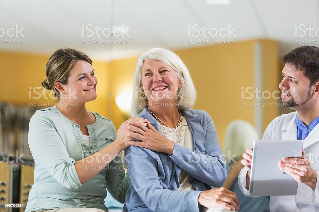 Woman with adult daughter talking to doctor stock photo