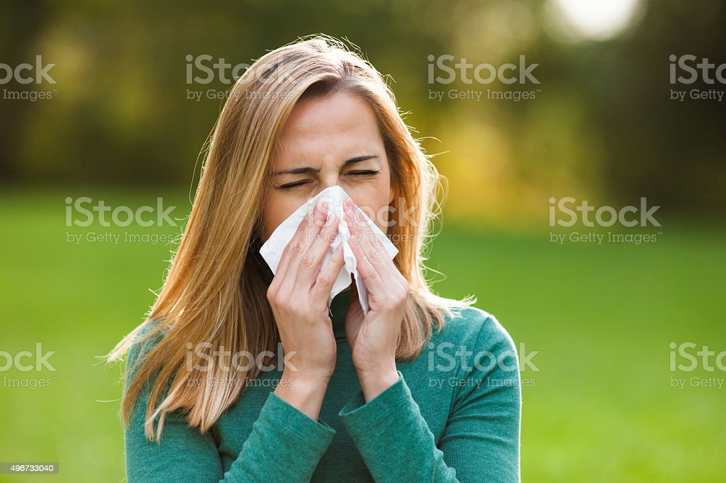 Woman with allergy symptom blowing nose stock photo