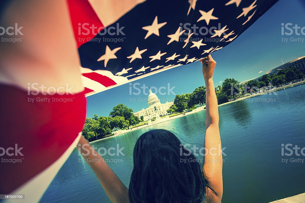 Woman with American Flag at Capitol Hill Building in Washington royalty-free stock photo
