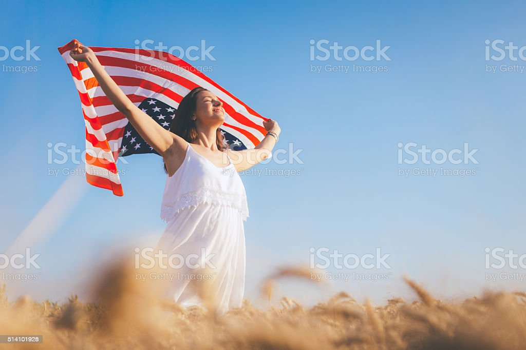 Woman with American flag flies proudly in the wheat stock photo