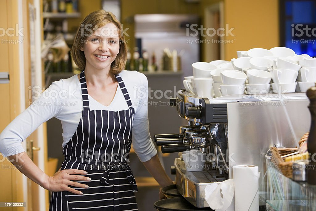 Woman with an apron on standing beside a coffee machine stock photo