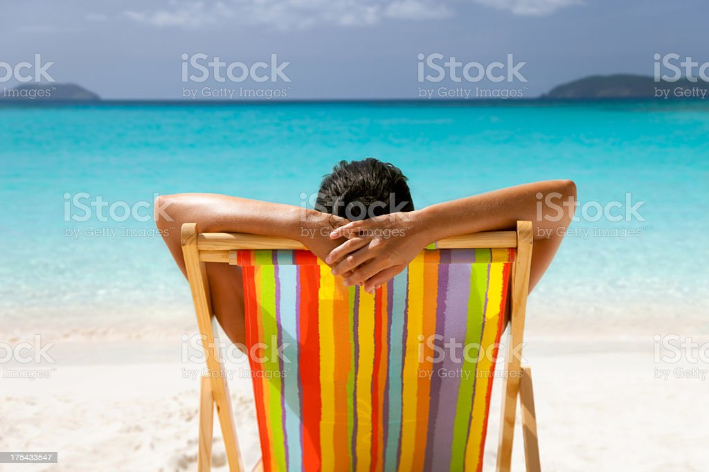 woman with arms behind her head sunbathing at tropical beach royalty-free stock photo