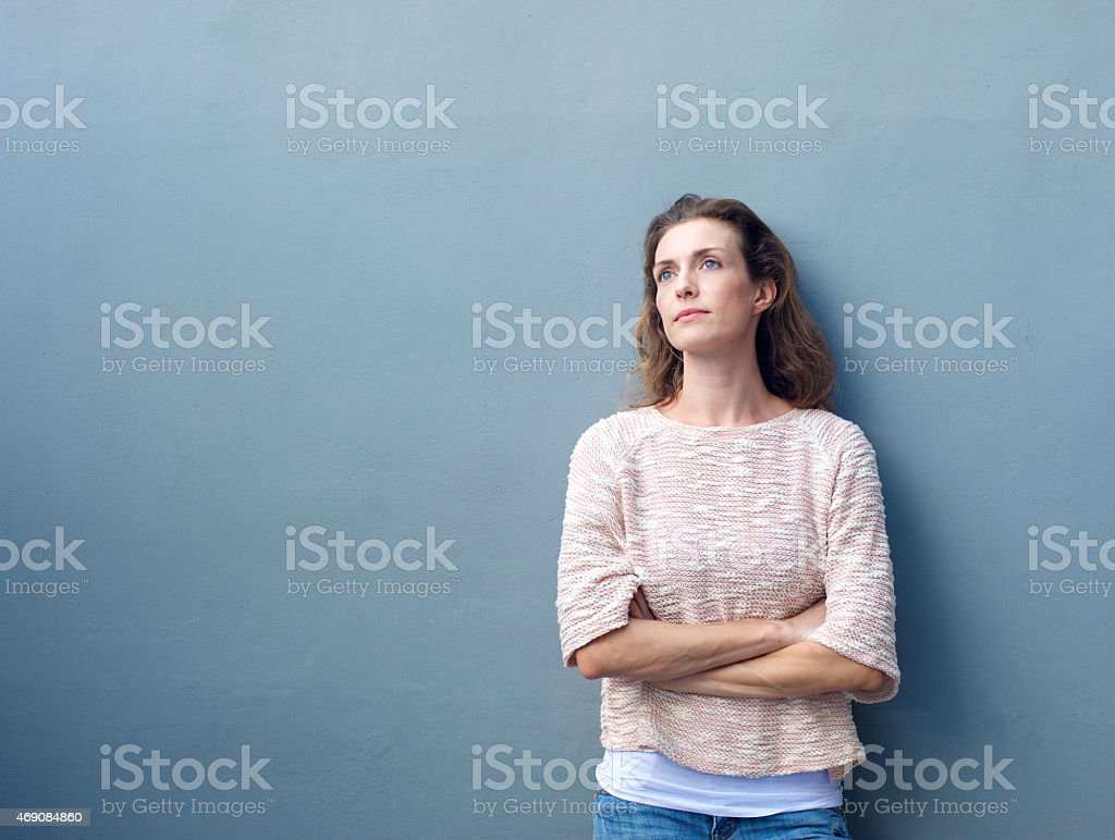 Woman with arms crossed looking away with thoughtful expression stock photo