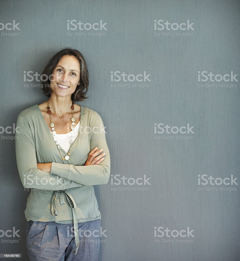 Woman with arms folded against gray background stock photo