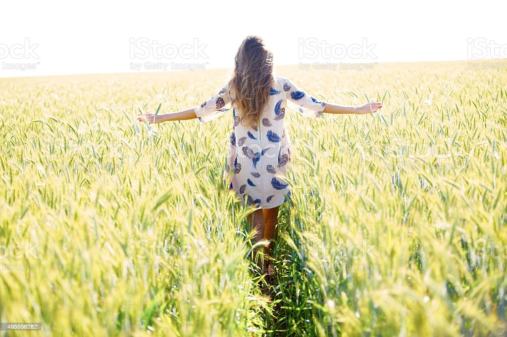 Woman with arms outstretched in wheat field stock photo