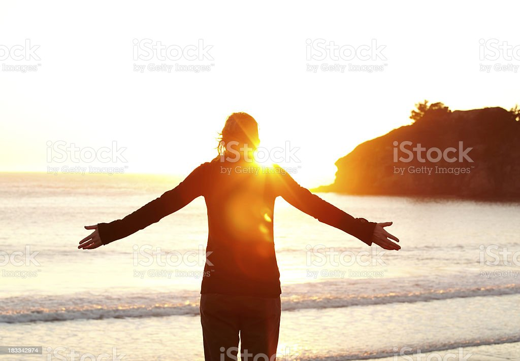 Woman with arms outstretched watching sunset stock photo
