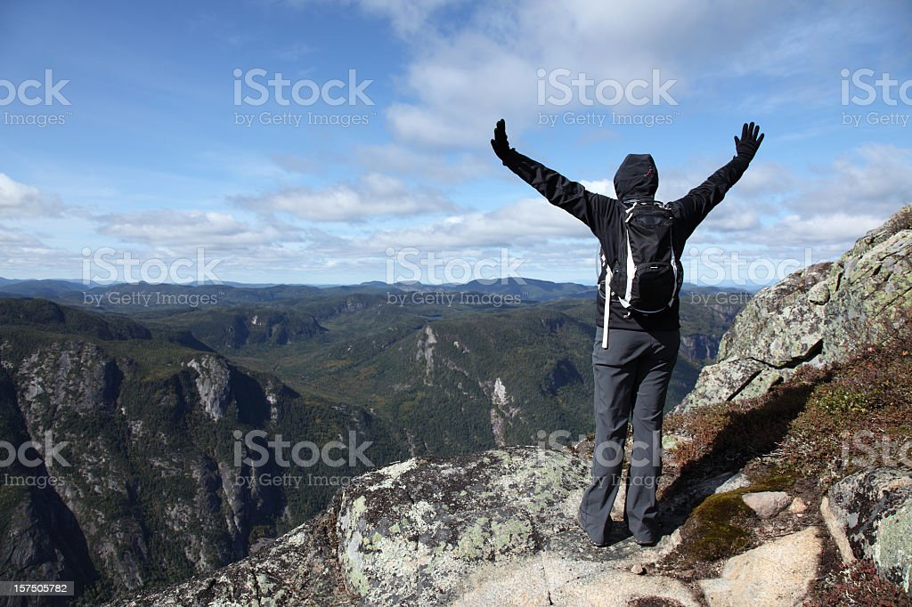 Woman with Arms Raised on Mountain Summit, Charlevoix, Quebec stock photo