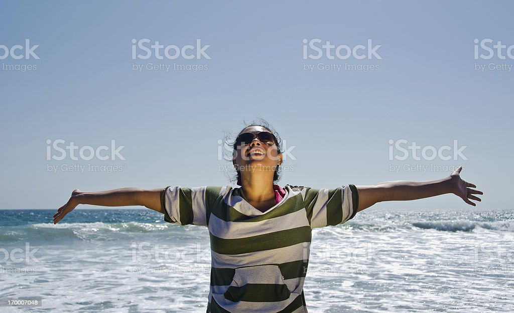 Woman with arms stretched looking at sky at the beach stock photo