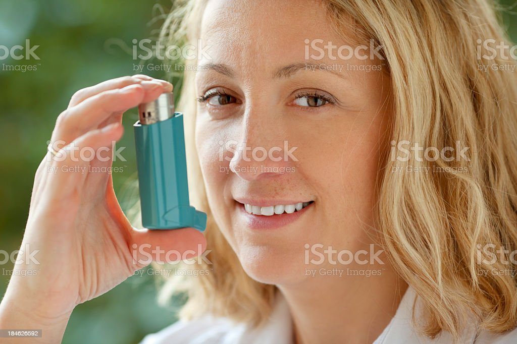 Woman With Asthma Inhaler Outdoor stock photo