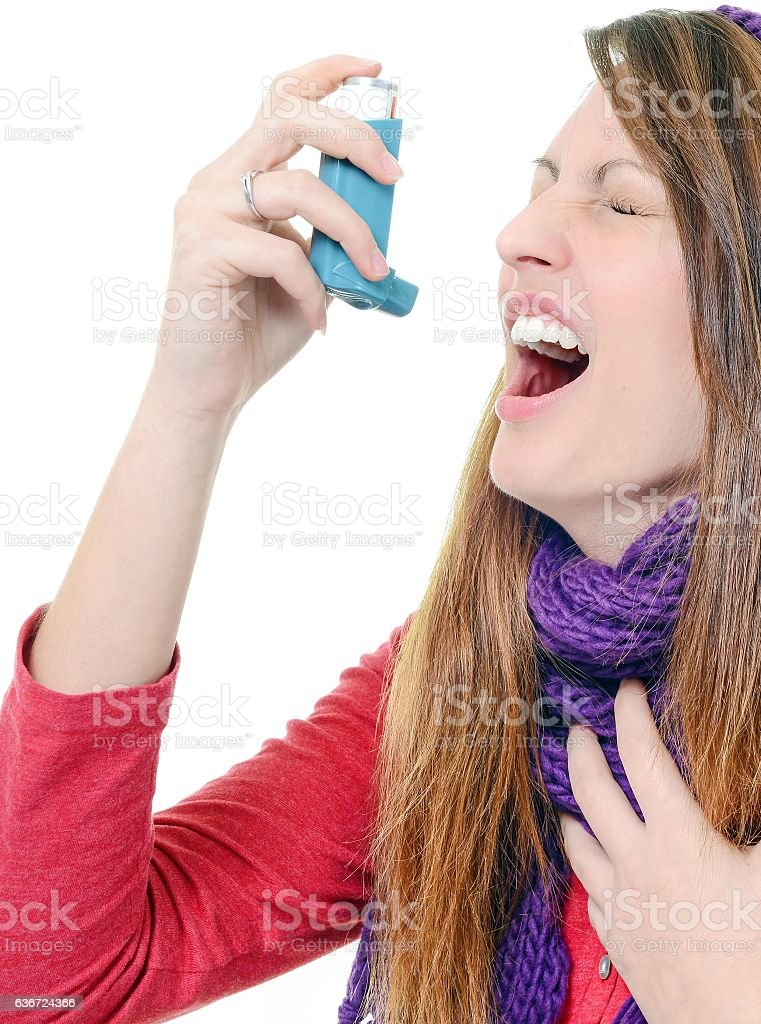 Woman with asthma using an asthma inhaler stock photo
