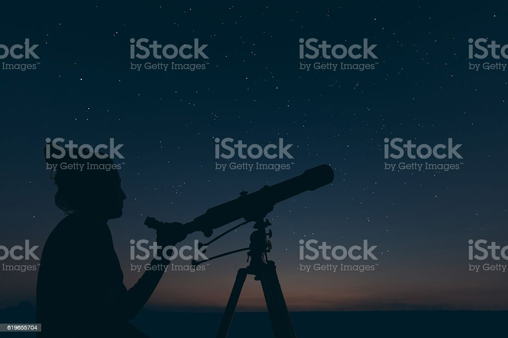 Woman with astronomical telescope. Starry night Constellations, stock photo