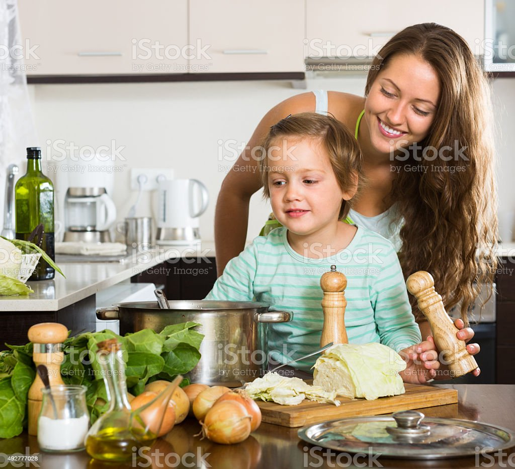 Woman with baby cooking at kitchen stock photo