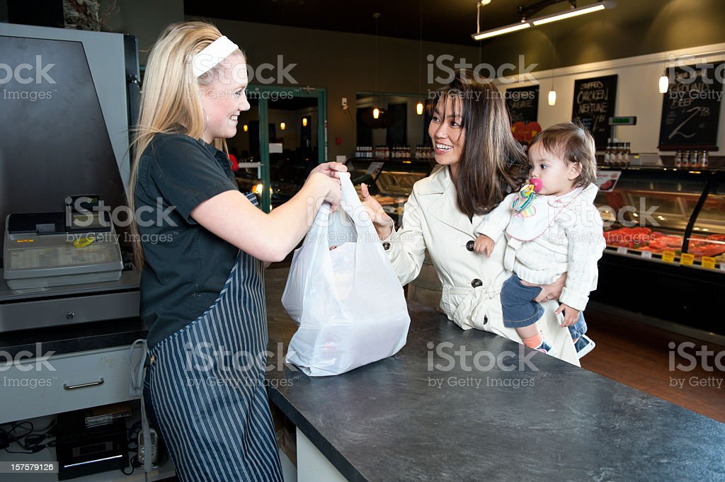 Woman with baby pictures grabbing bag from female employee stock photo