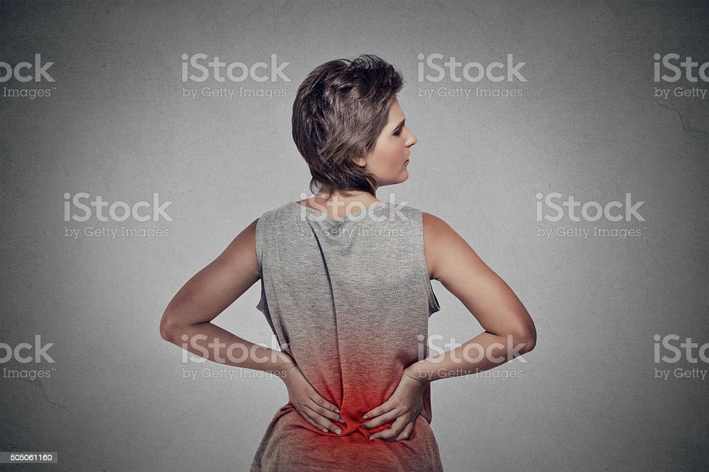 Woman with backache lower back pain colored in red stock photo