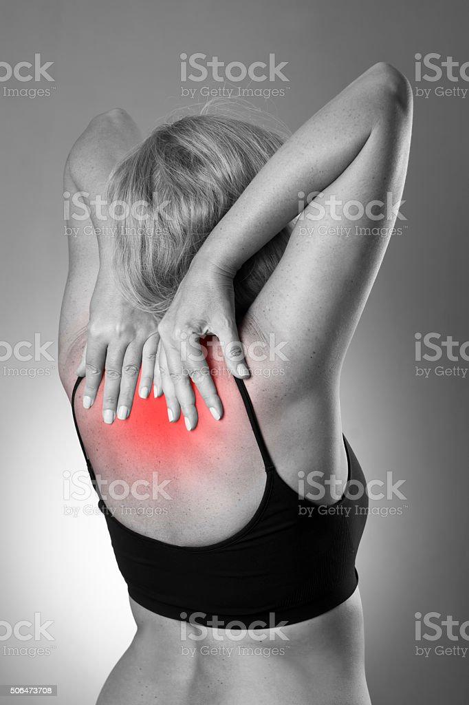 Woman with backache on a gray background stock photo