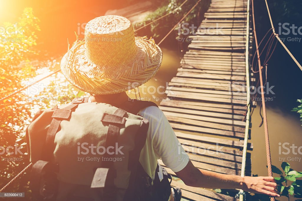 Woman with backpack and hat traveling across danger hanging bridge stock photo