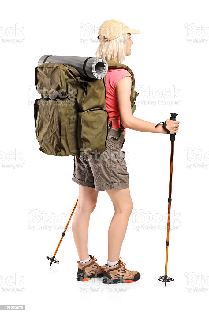 Woman with backpack and hiking poles posing royalty-free stock photo