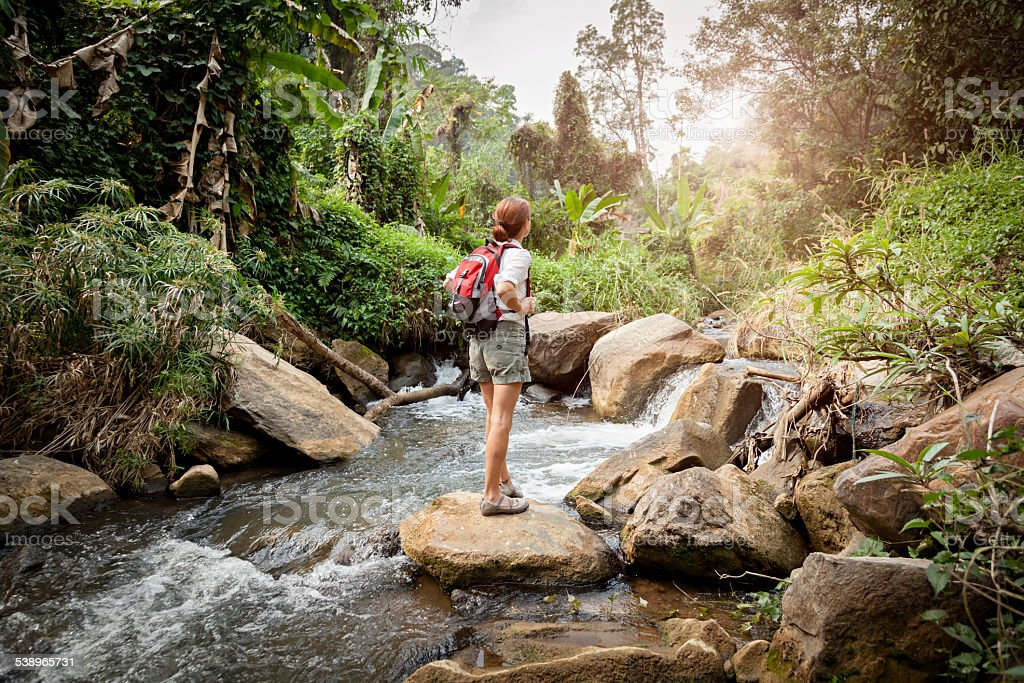 Woman with backpack hiking at rainforest river stock photo