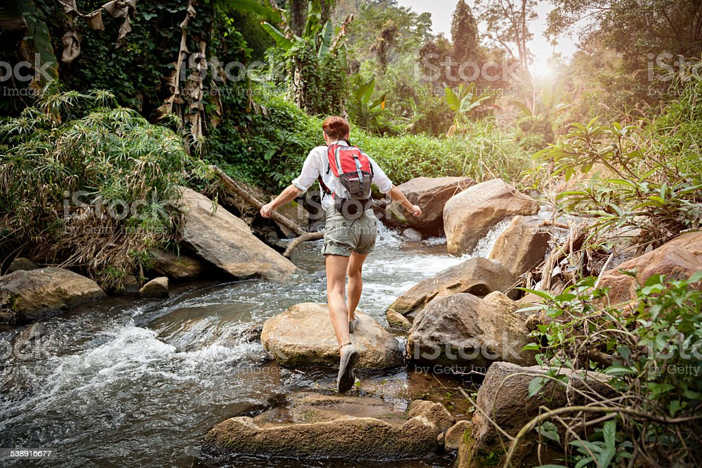 Woman with backpack hiking in rainforest stock photo