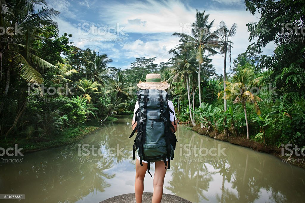 Woman with backpack near tropical river stock photo