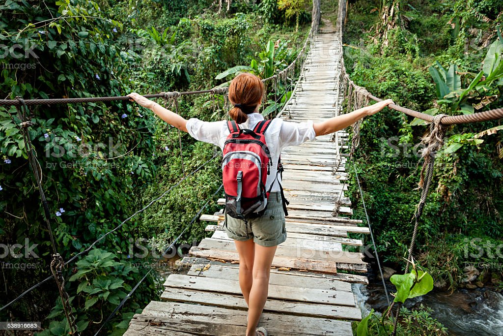 Woman with backpack on suspension bridge in rainforest jungle stock photo