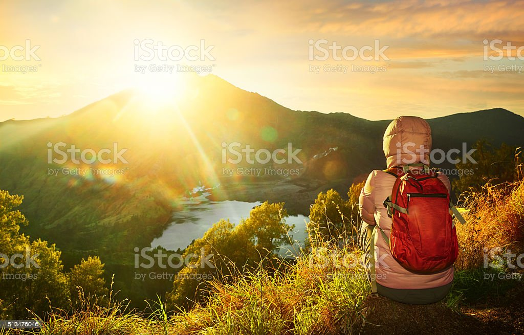 Woman with backpacker enjoying sunrise view at high mountains. stock photo