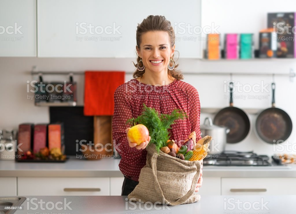 Woman with bag of fresh produce holding up an apple stock photo
