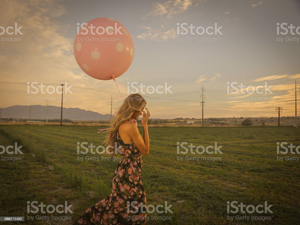 Woman with balloon in field crying stock photo