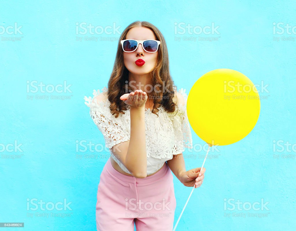 woman with balloon sends an air kiss over blue stock photo