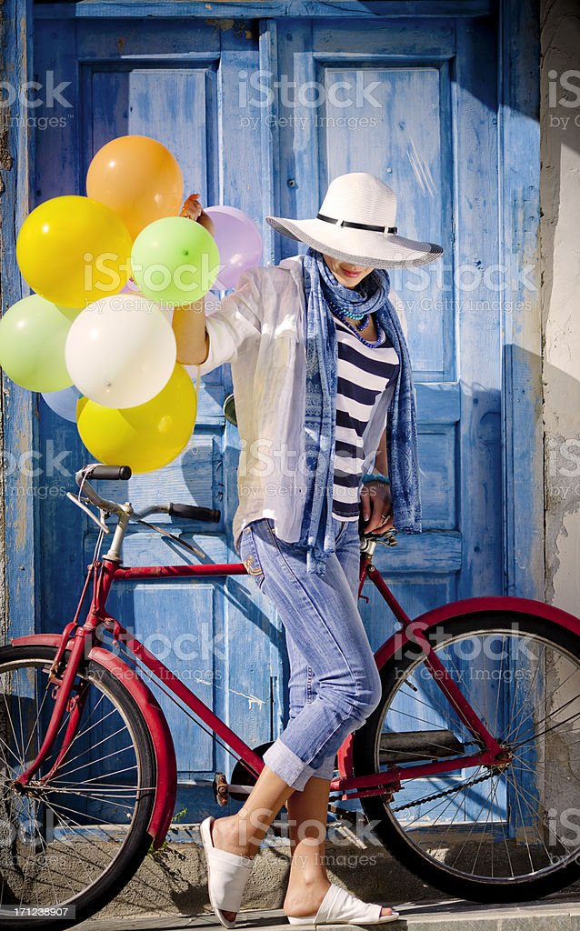 Woman with balloons standing her classic bicycle royalty-free stock photo