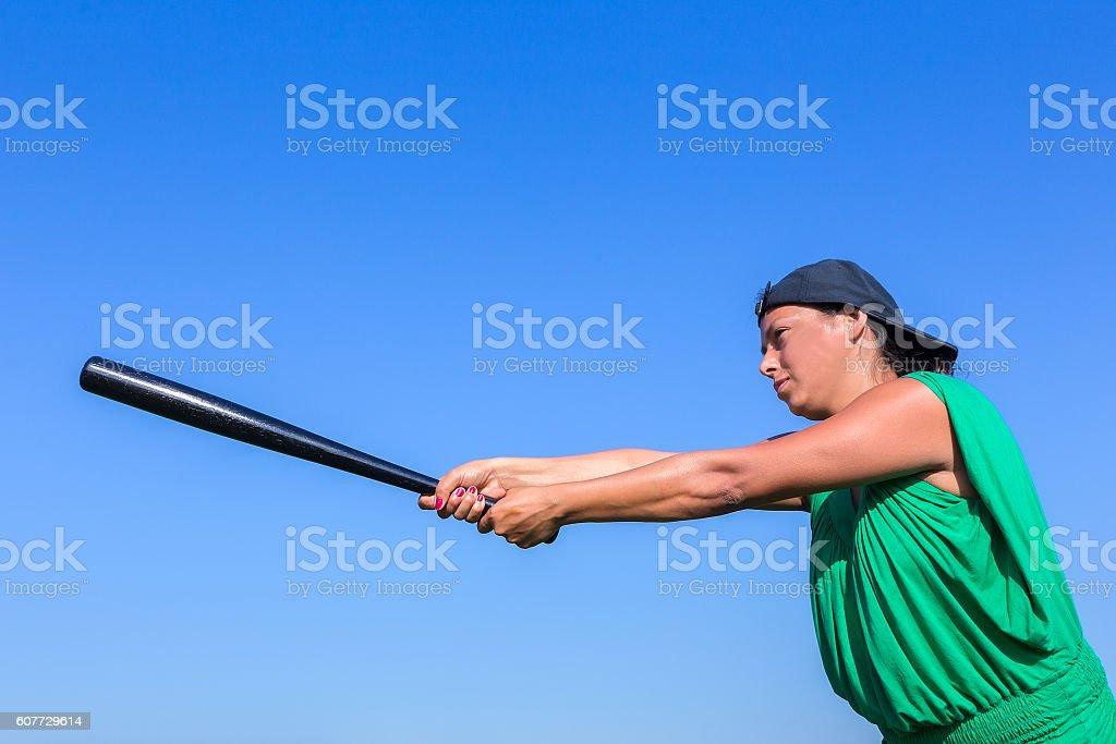 Woman with baseball bat body posture to strike stock photo